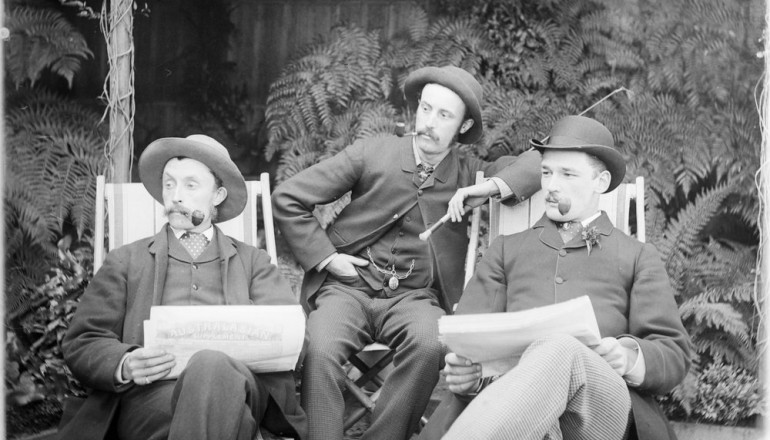 Three men sitting in deck chairs, smoking pipes and reading papers by State Library of Victoria